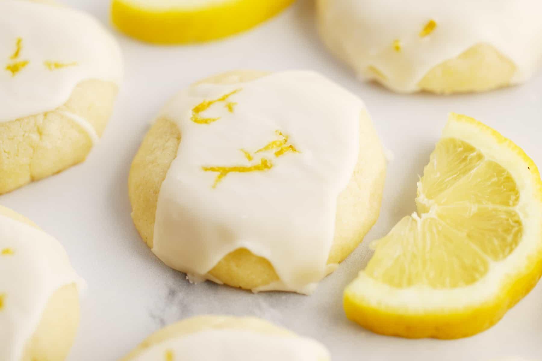 Glazed cookies on a tabletop garnished with lemon zest.