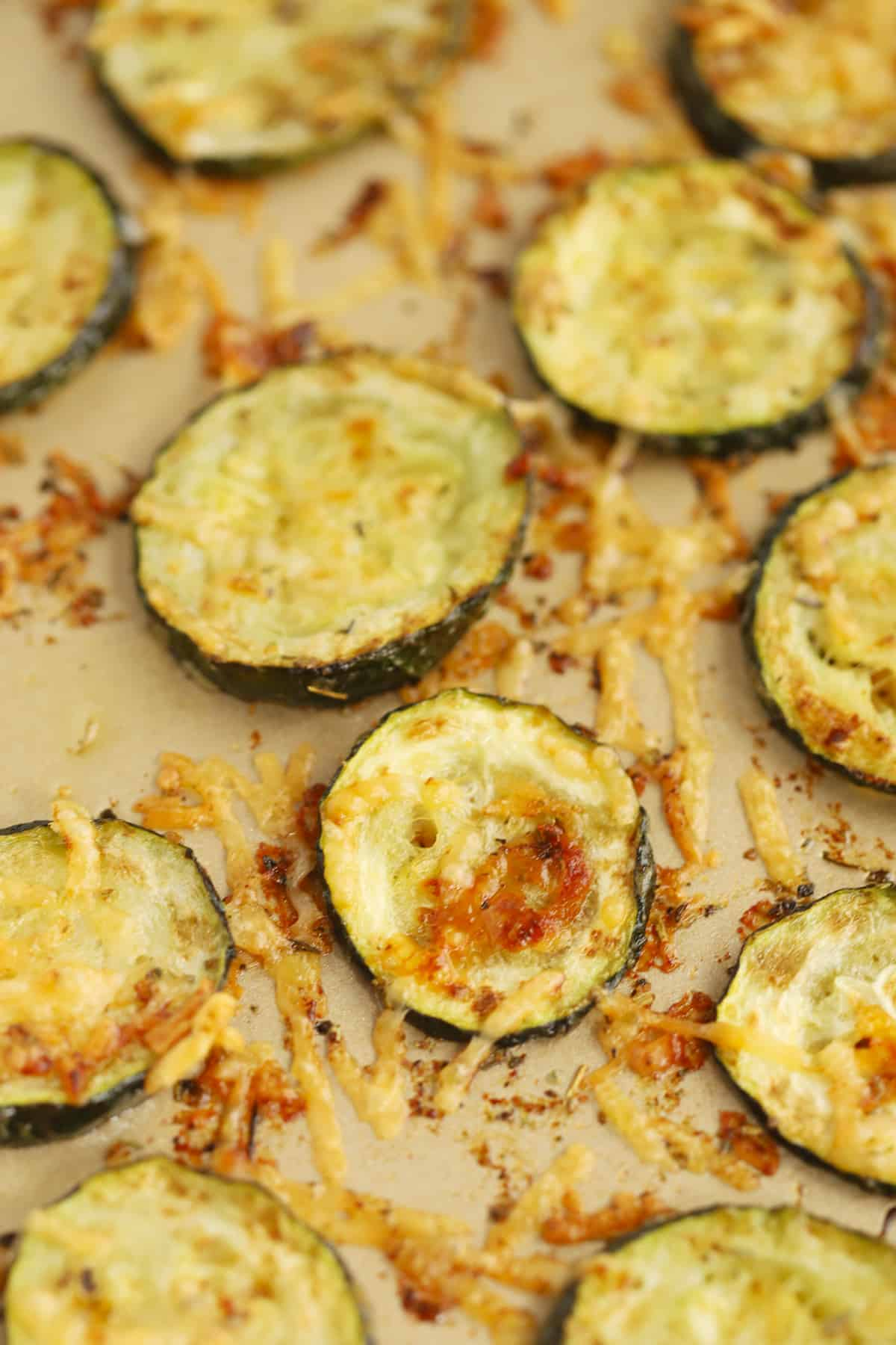 Bake zucchini rounds covered with crispy golden brown Parmesan cheese.