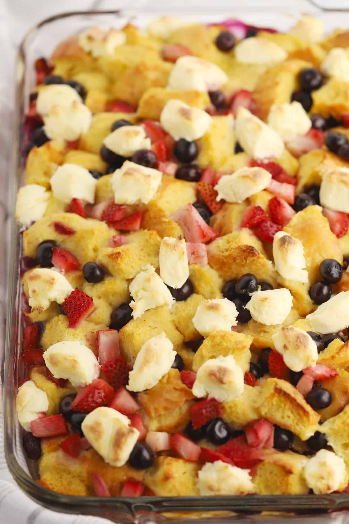 French toast bake topped with blueberries, strawberries and cream cheese.