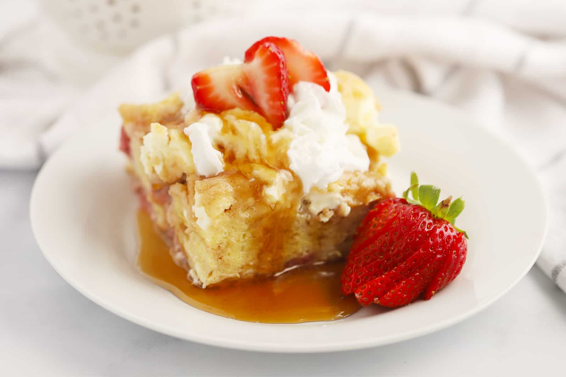 A white plate with a slice of French toast bake topped with whipped cream, strawberries and syrup.