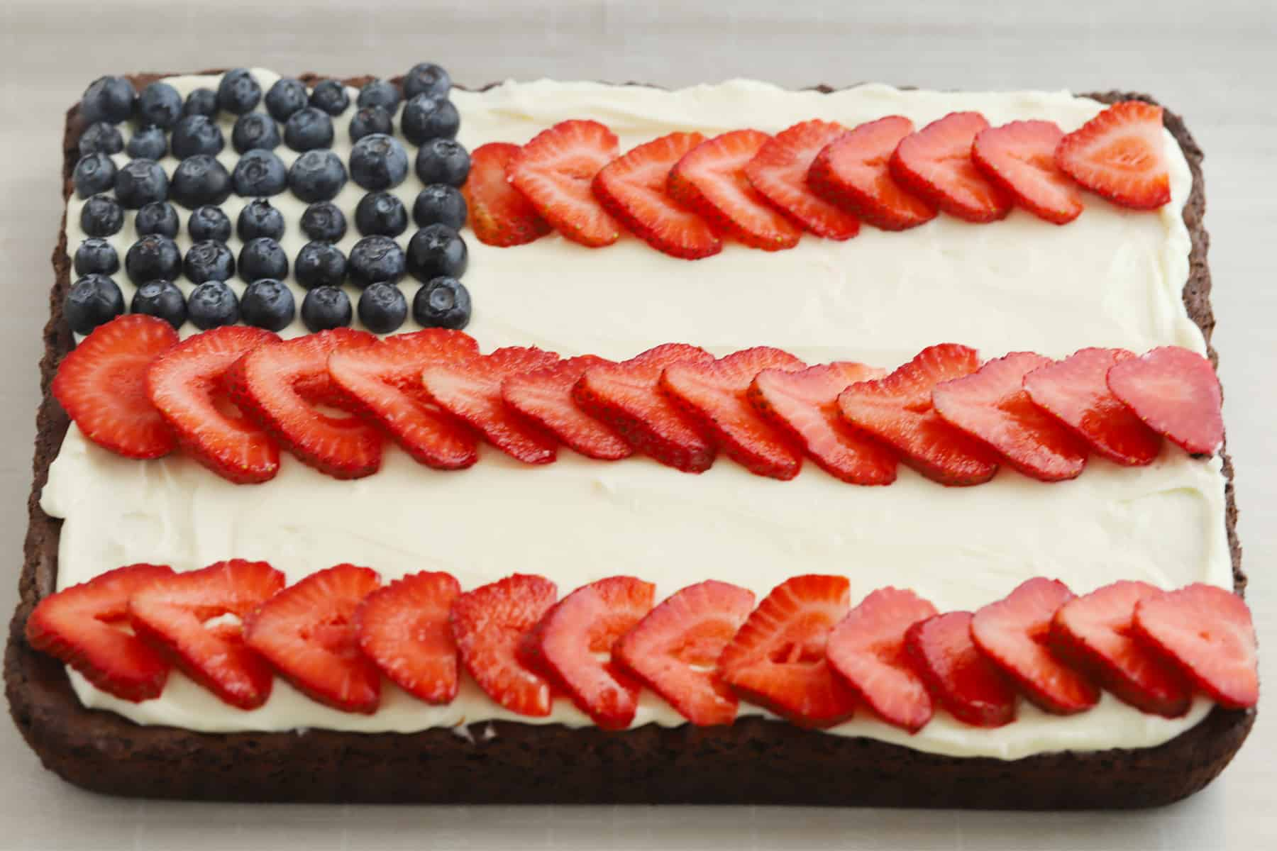 A large brownie topped with blueberries and strawberries and decorated to look like the American Flag.