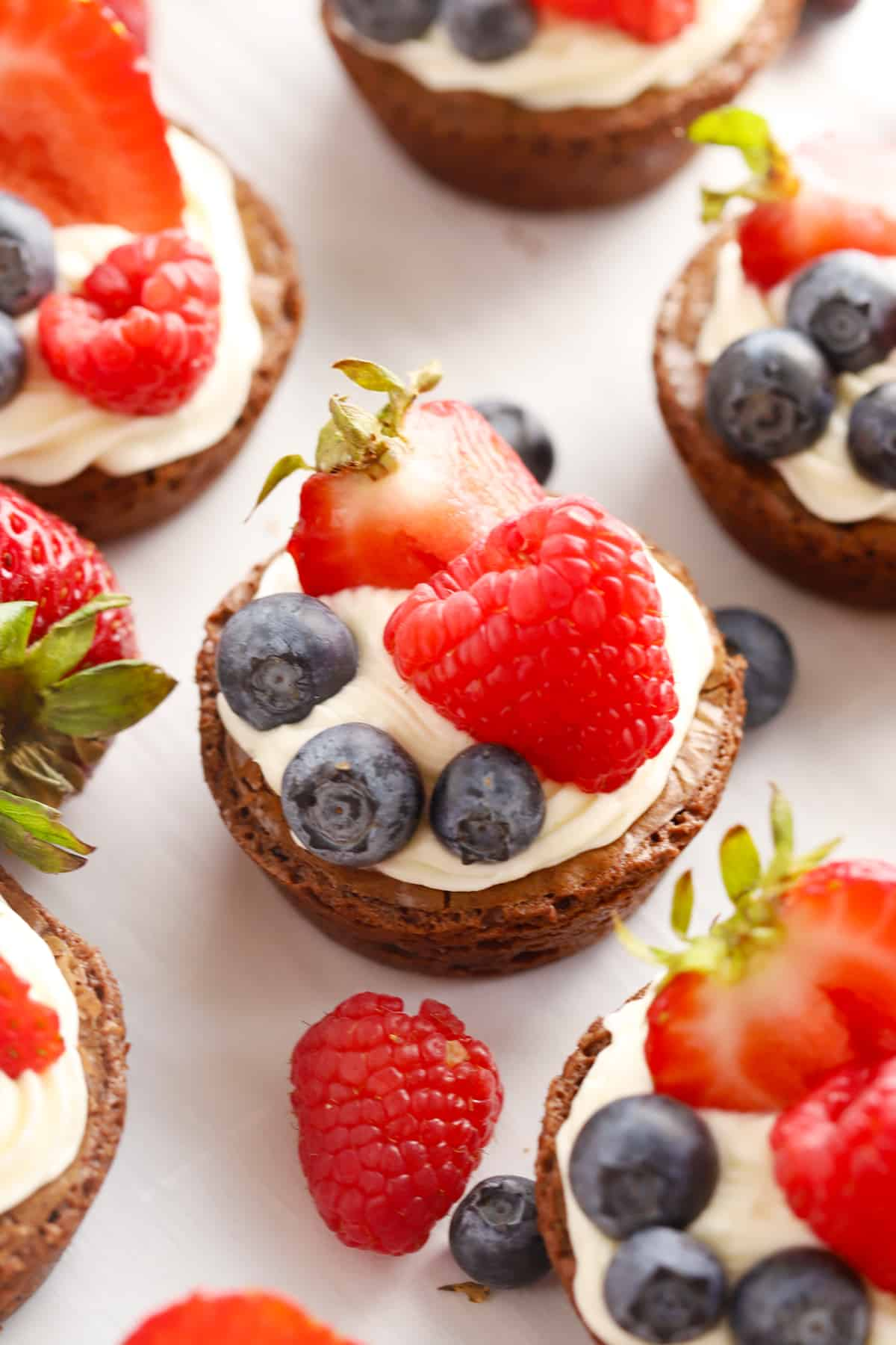 Mini brownie bites on a table topped with cream cheese frosting and fresh berries.