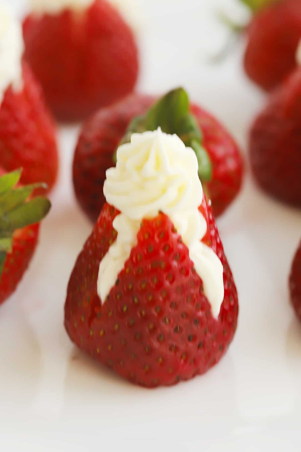 Strawberries cut open and stuffed with cream cheese filling.