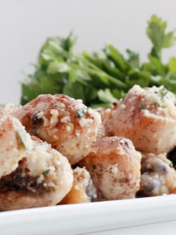 garlic parmesan drumsticks with a sprig of parsley on a white platter