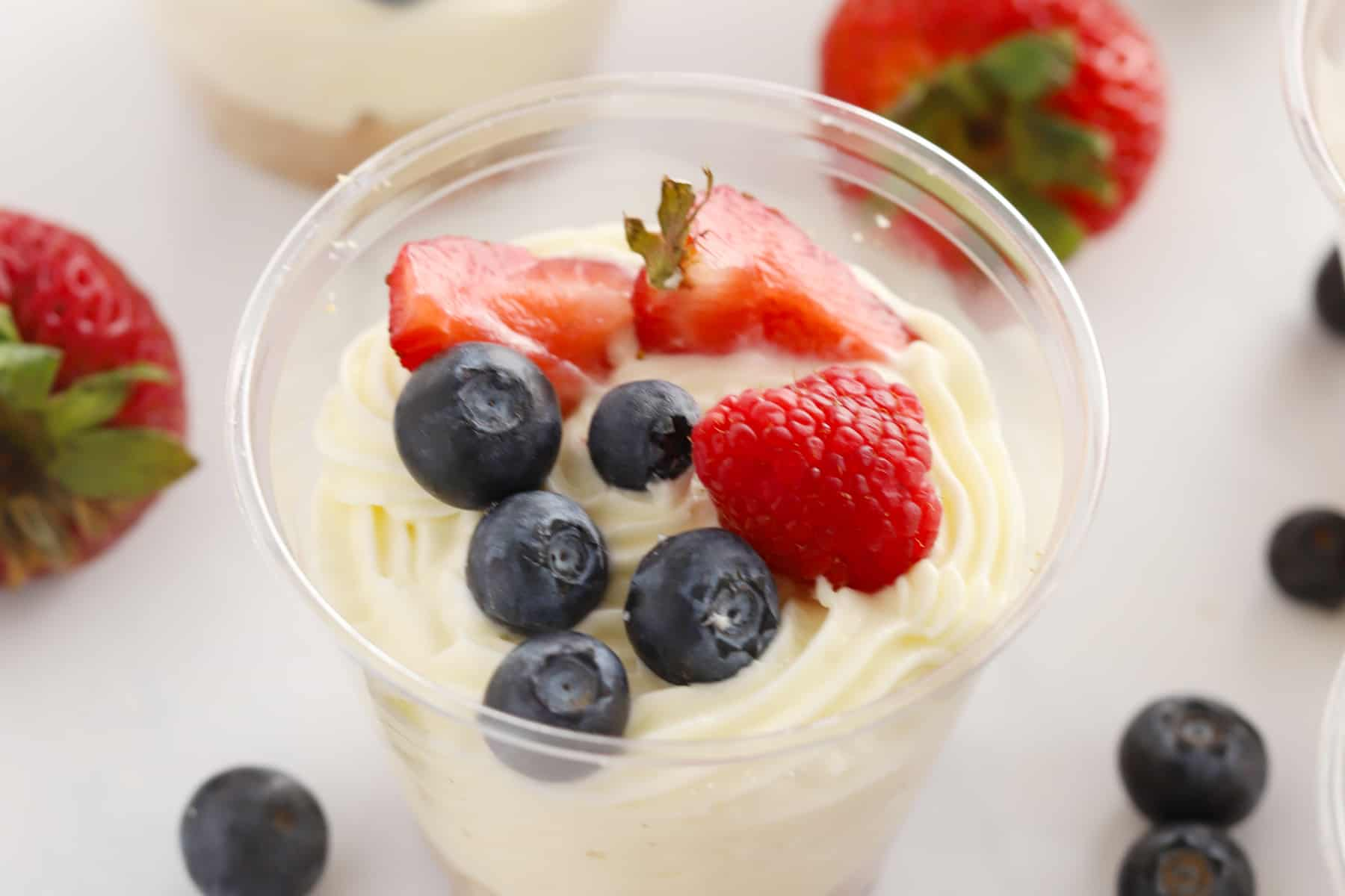 A close-up photo of no-bake cheesecake in a plastic cup topped with fresh strawberries, raspberries and blueberries.