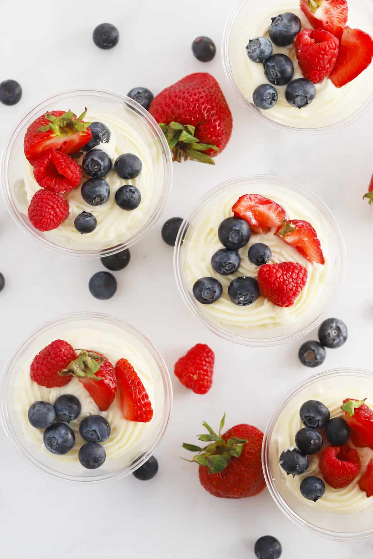 Individual cheesecakes in plastic cups, topped with fresh strawberries and blueberries.