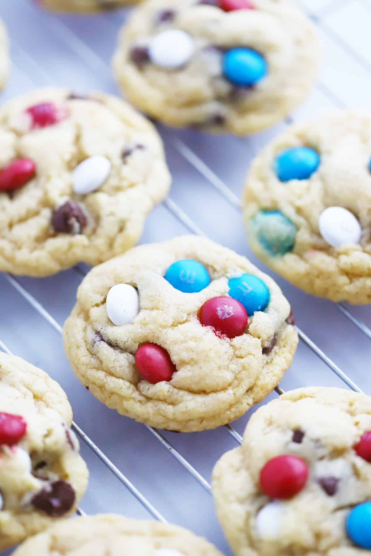 Cookies with red, white and blue M&Ms cooling on a wire rack.
