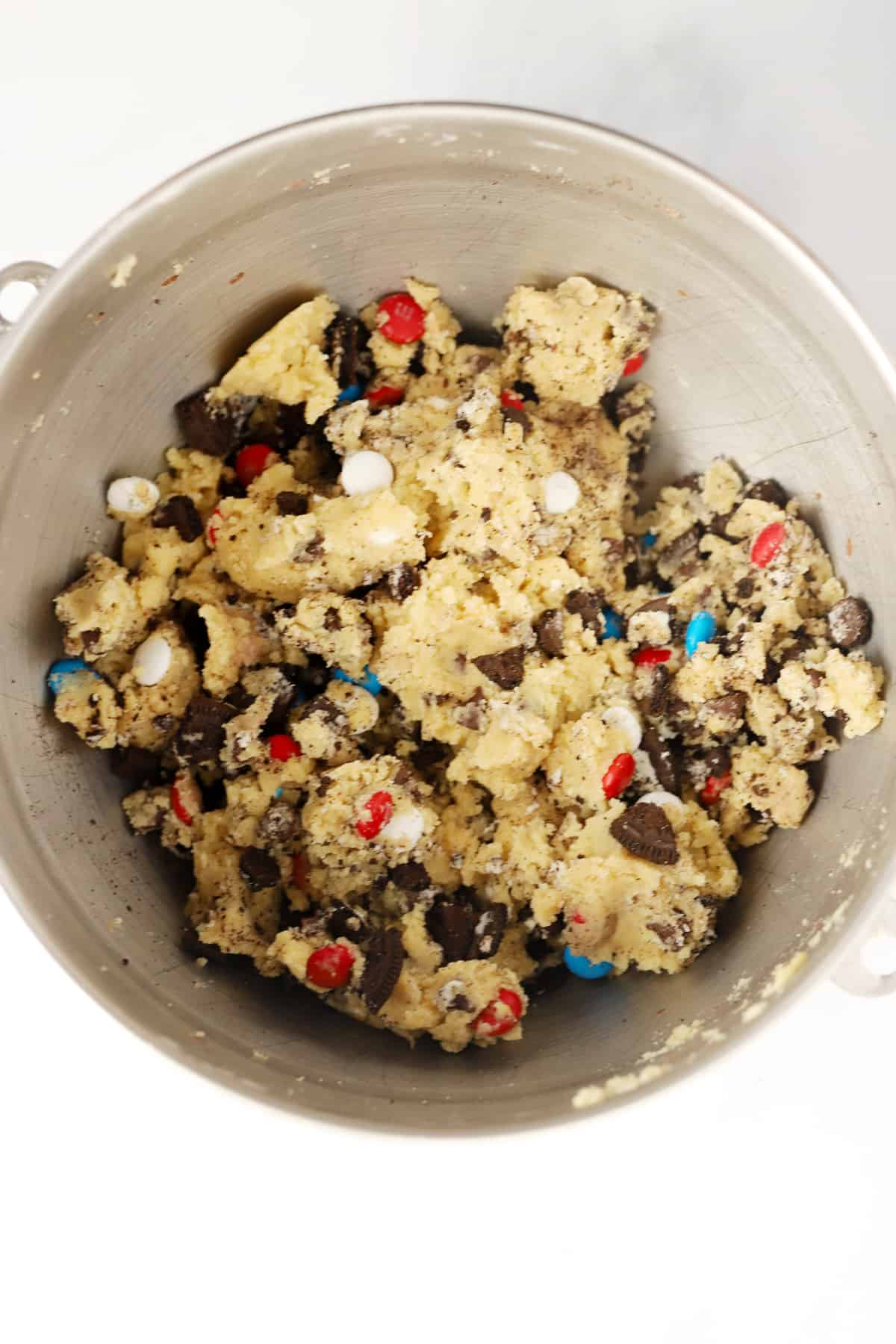 A mixing bowl full of cookie dough with chocolate chips, Oreo pieces and M&Ms.