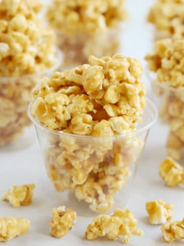 Caramel popcorn inside plastic cups on a table.