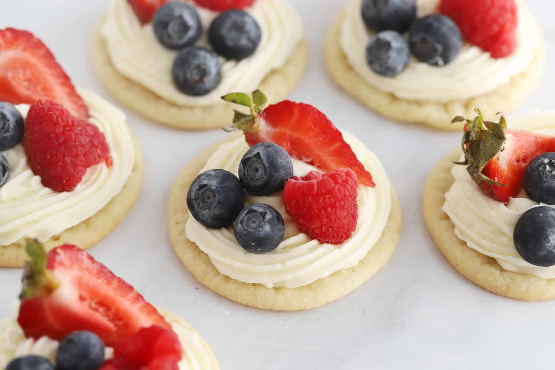 Individual sugar cookies topped with frosting and fresh berries.