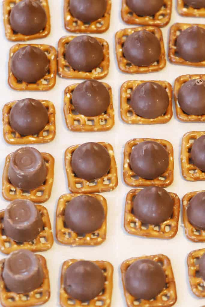 Square pretzels topped with melted Rolos on a sheet tray.