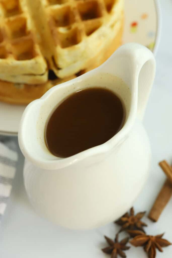 Syrup in a small white pitcher with waffles in the background.