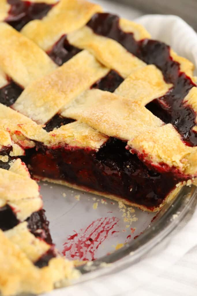 A lattice-top pie in a pie dish with a slice removed.