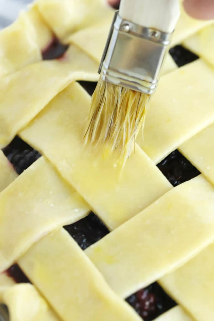A brush adding egg wash to an unbaked lattice top pie shell.