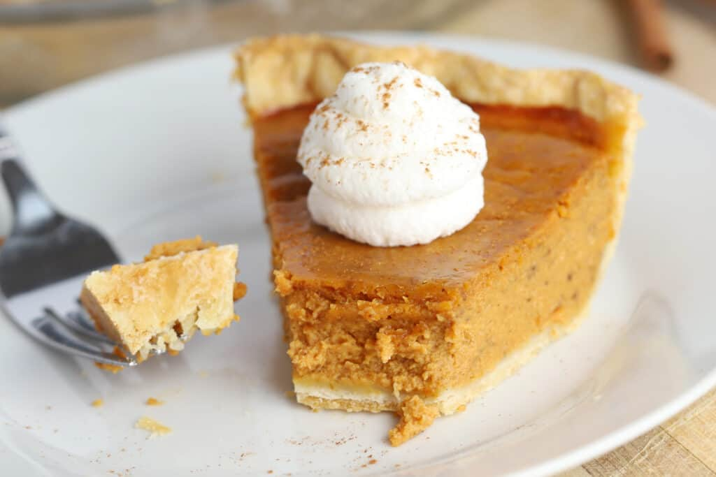 A white plate with a slice of pumpkin pie, topped with whipped cream and a fork with a piece of pie on it.