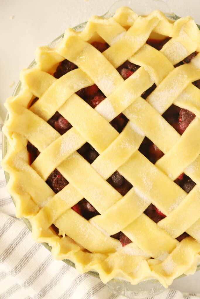 An unbaked pie with a lattice top design.