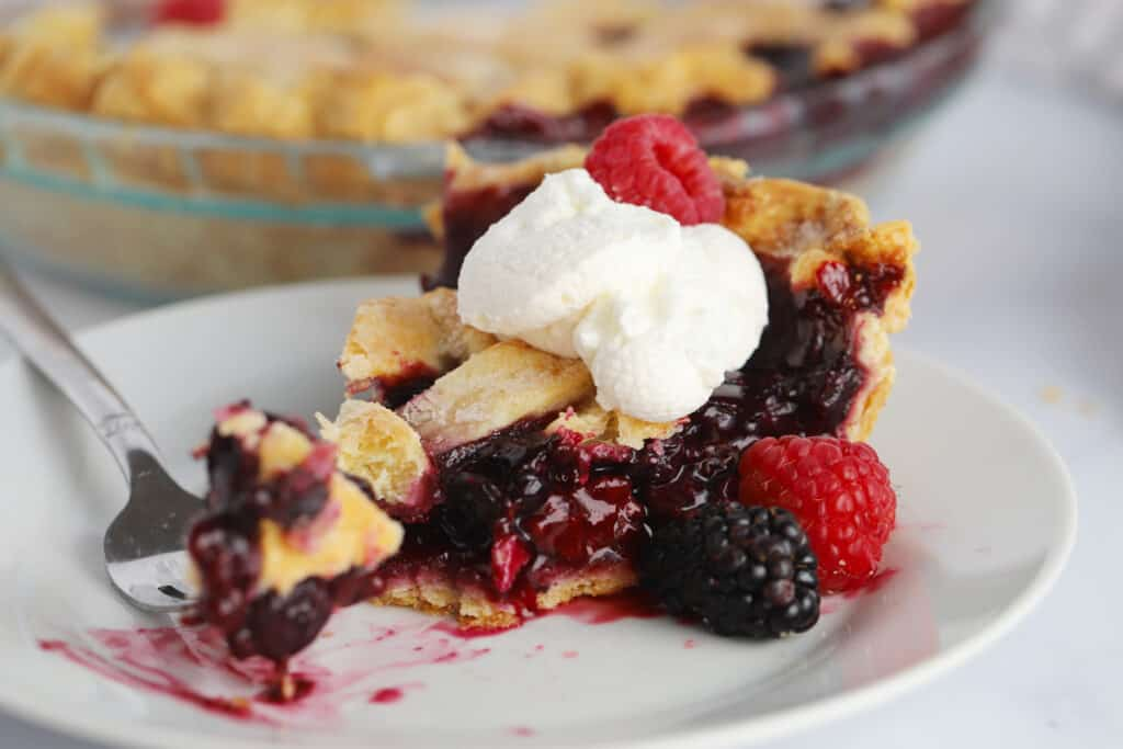 A slice of berry pie topped with whipped cream and fresh berries on a white plate.