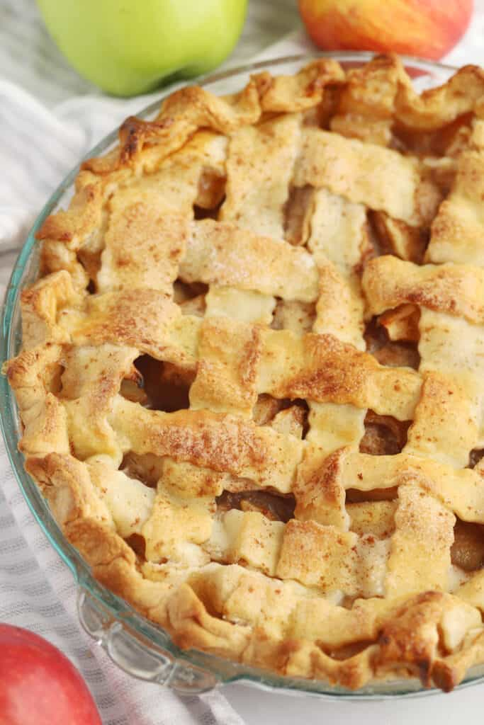 A fresh baked apple pie in a glass pie plate on a table.