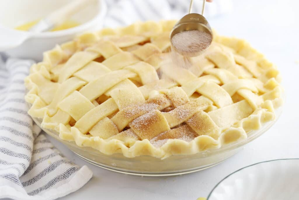 An unbaked lattice-top pie being sprinkled with cinnamon sugar.