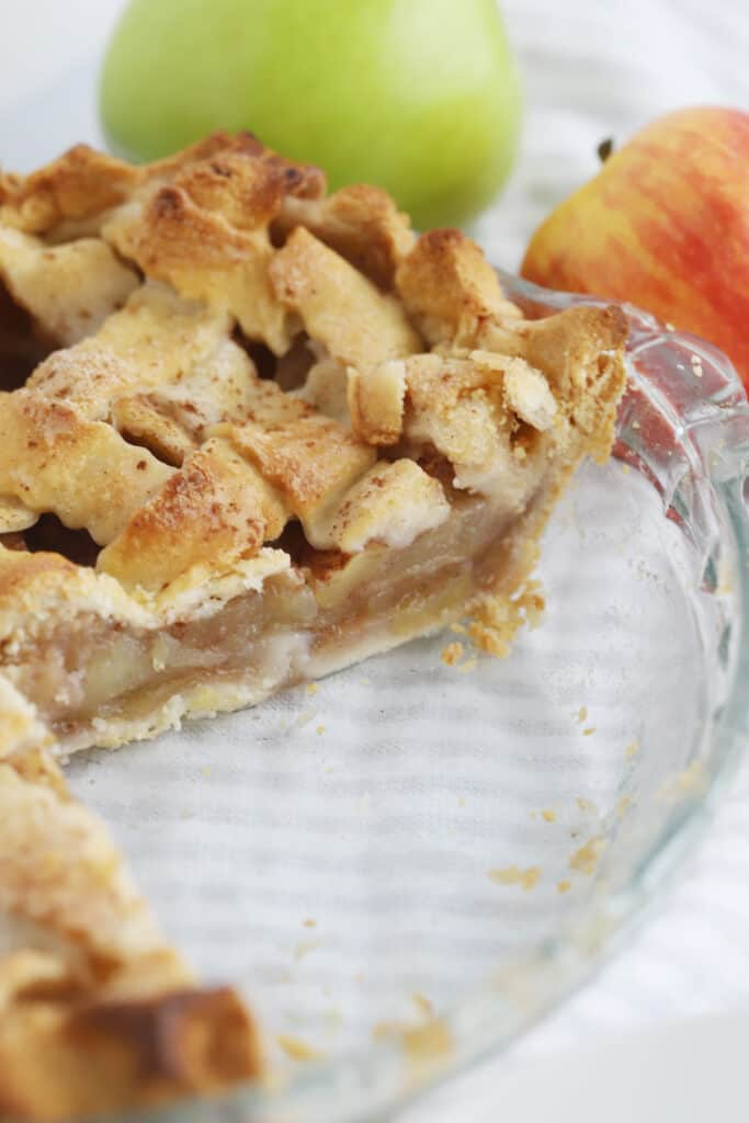 A glass pie plate with an apple pie that has a slice removed.