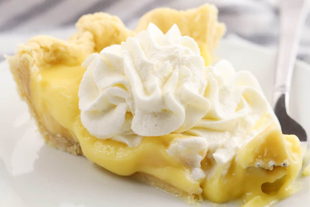banana cream pie with whipped cream on a white plate