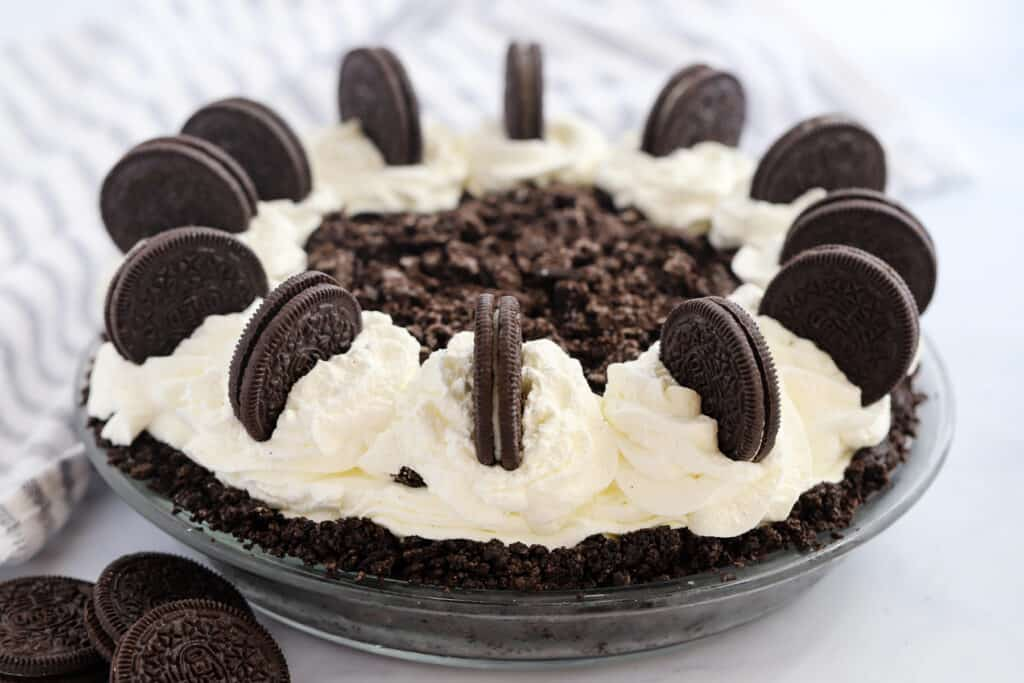 A full chocolate pie in a glass pie dish topped with whipped cream and decorated with Oreo cookies.