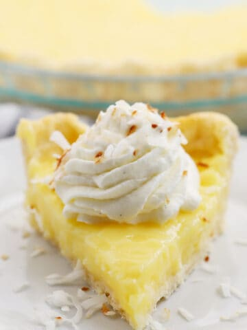 a slice of coconut cream pie on a white plate