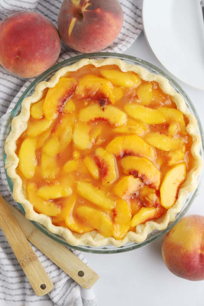A photo from above of a peach pie on a table surrounded by fresh peaches.