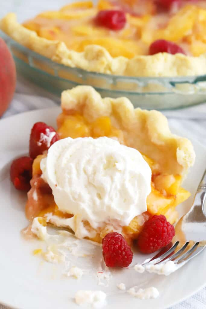 A slice of pie on a plate being eaten with a fork, and topped with fresh whipped cream and raspberries.