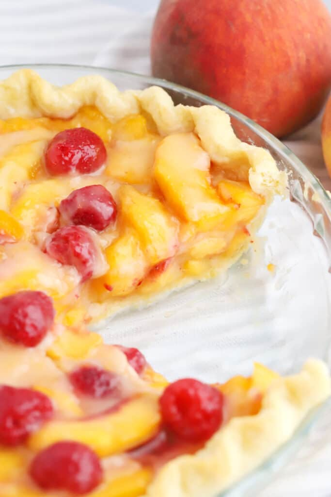 A fresh peach pie with raspberries in a pie plate with a slice removed.