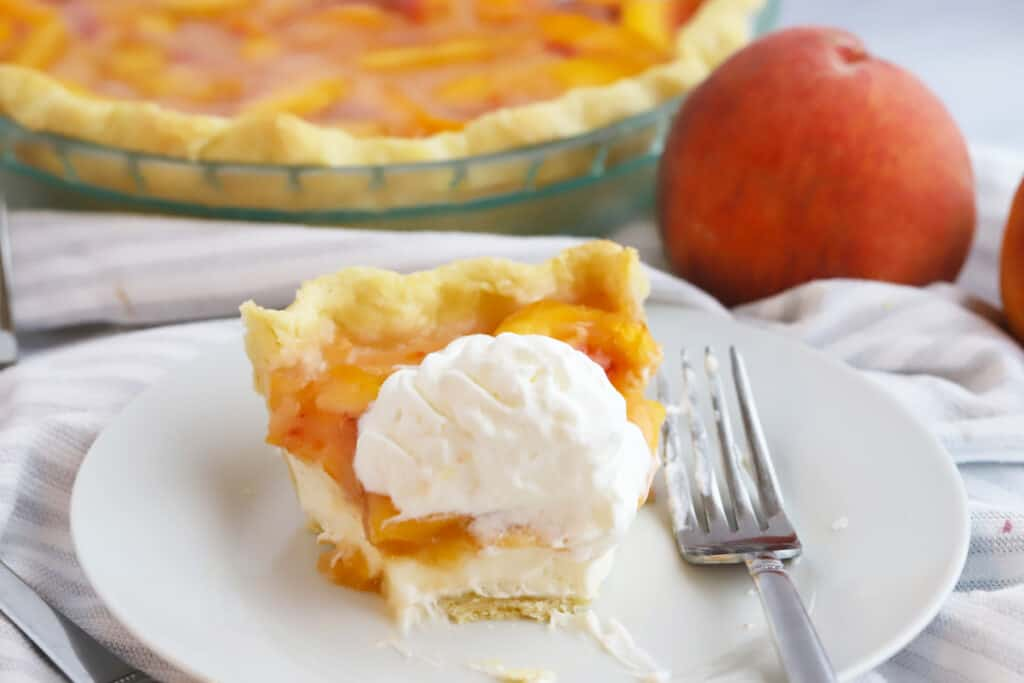 A slice of peach pie on a plate topped with whipped cream with a bite taken out of it.