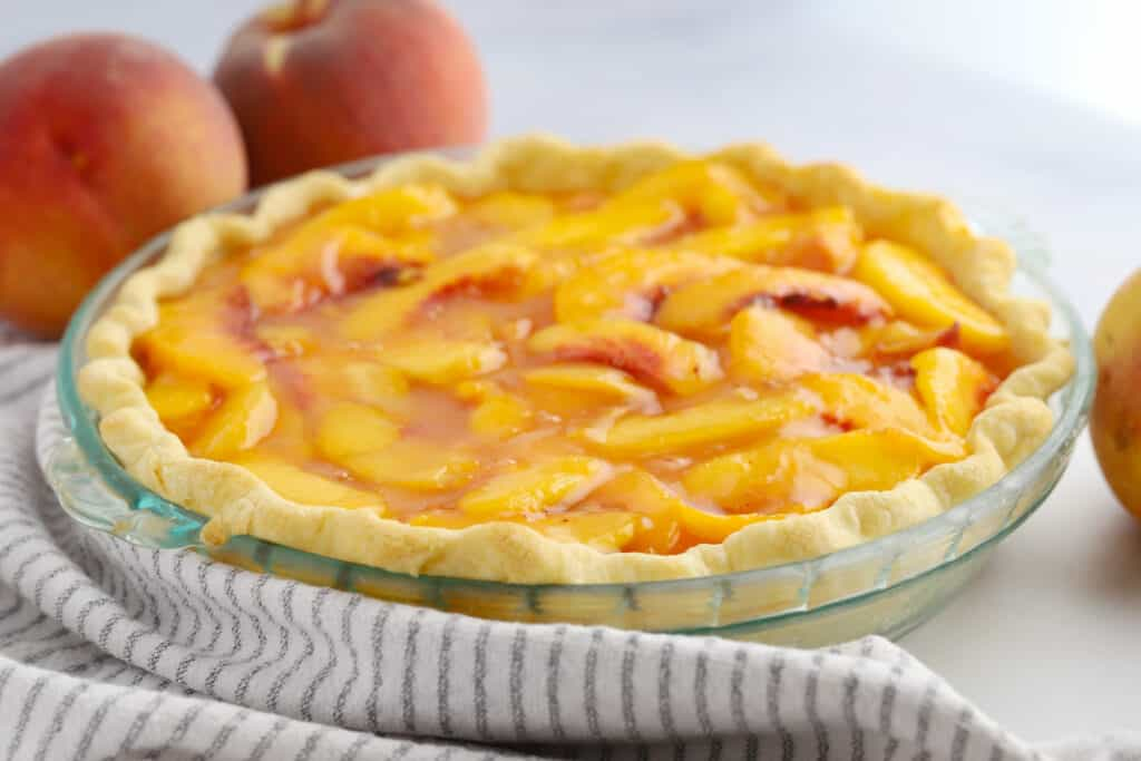 A pie in a pie dish topped with fresh peaches.