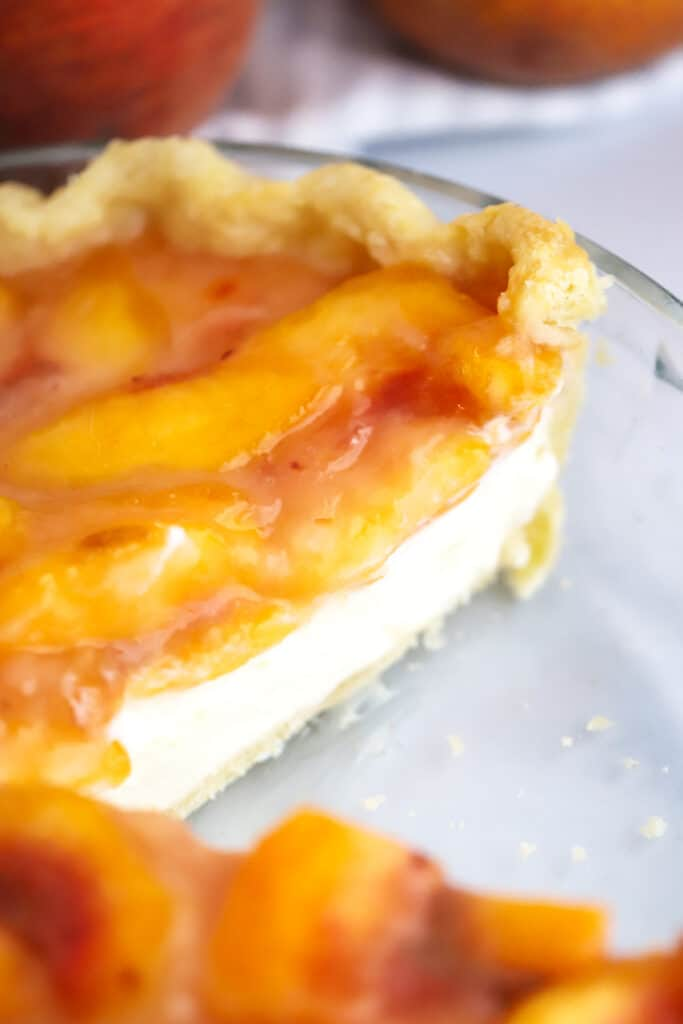 A pie filled with peaches and cream in a pie plate with a slice removed.