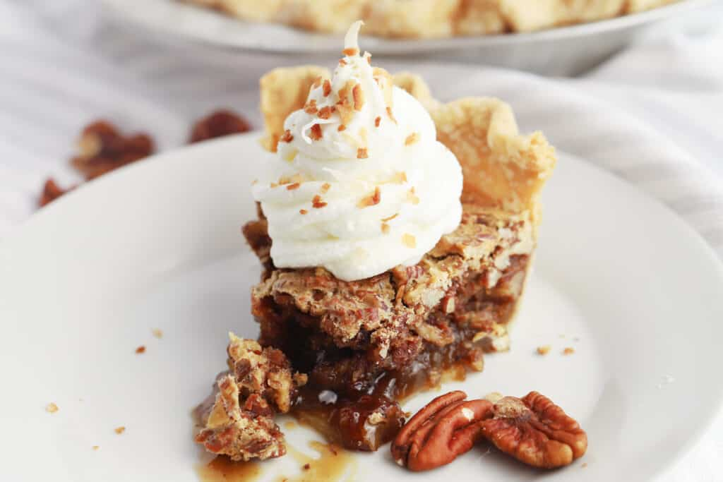A slice of pecan pie on a white plate topped with whipped cream and more pecans.