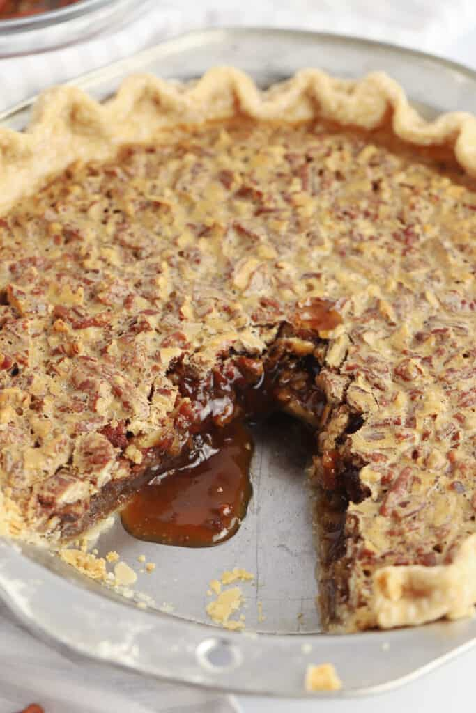 A pecan pie with a slice removed and caramel oozing out.