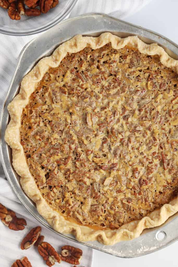 The top view of a full pecan pie in a pie plate.