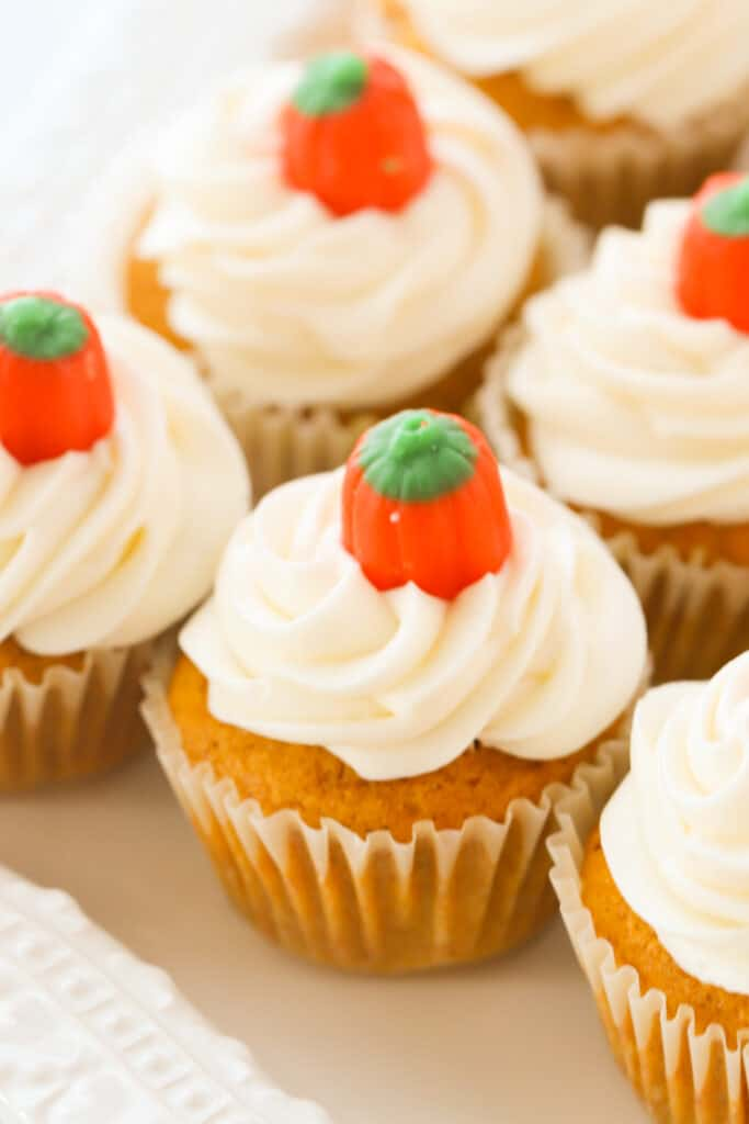 Cream cheese frosted pumpkin cupcakes lined up on a table and garnished with little candy pumpkins.
