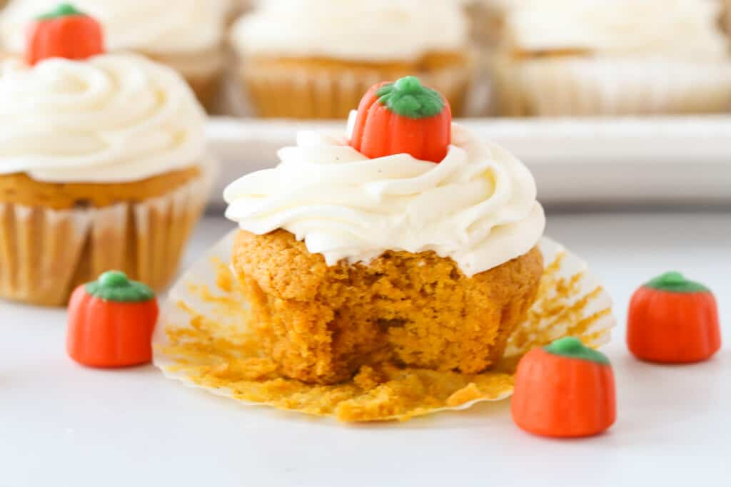 A pumpkin cupcake, topped with frosting and a candy pumpkin, with a bite taken out of it.